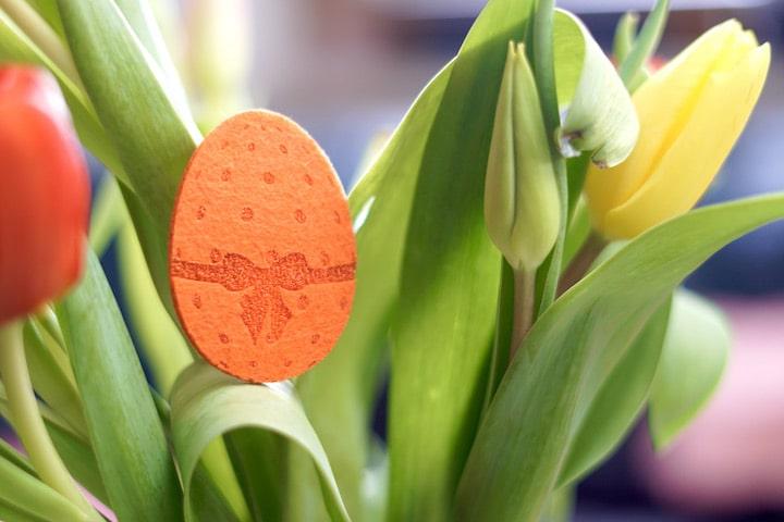 Oranges Osterei aus Filz in einem Blumenstrau%C3%9F aus Tulpen