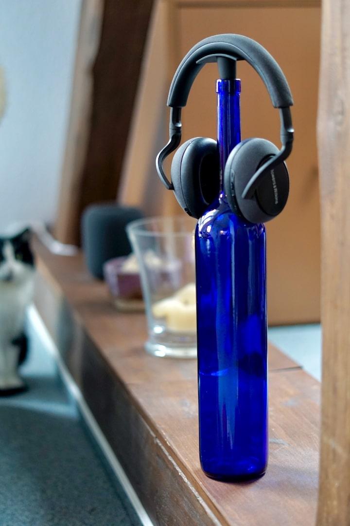 BeatsBuddy und Kopfhoerer auf einer blauen Flasche mit einer Katze im Hintergrund