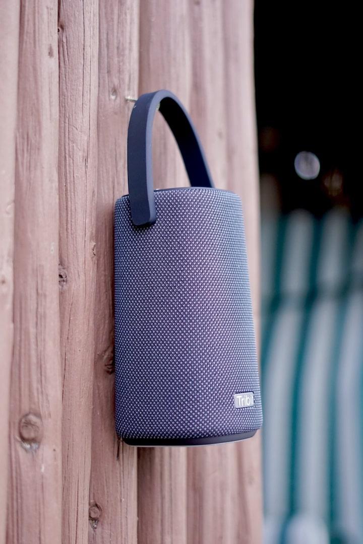 Bluetooth Lautsprecher haengt an einer Holzwand