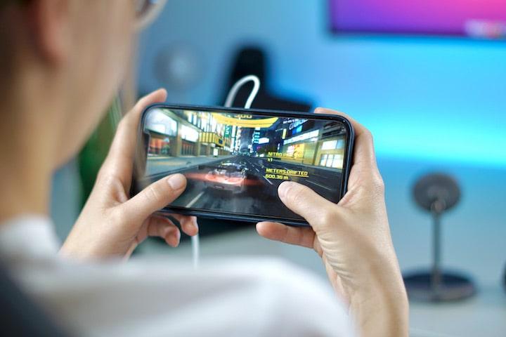 Frau mit Smartphone in der Hand spielt ein Racing Game