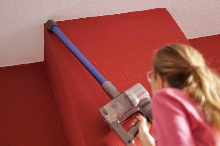 Frau saugt Zimmerdecke ab
