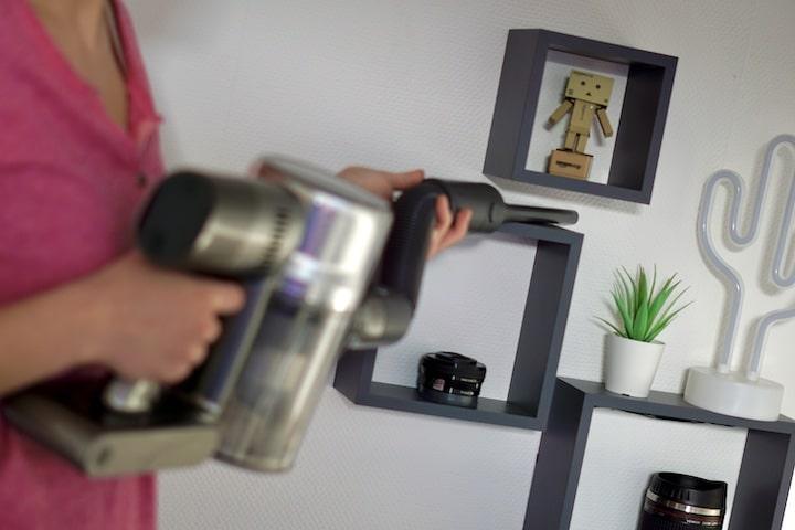 Frau saugt mit Akkusauger ein Regal ab