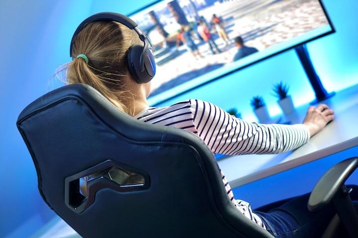 Frau sitzt auf einem Gaming Stuhl und zockt und spielt an einem PC