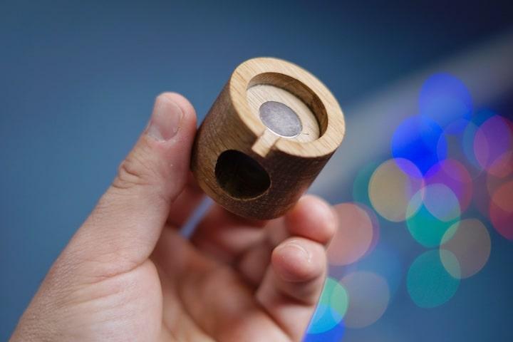 Hand haelt ein Stueck rundes Holz fest