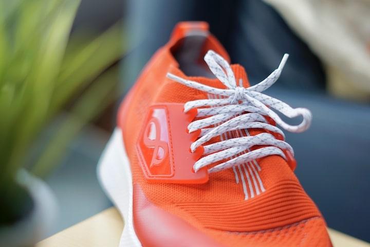 Roter Schuh mit wei%C3%9Fen Schnuersenkeln steht vor einer Pflanze