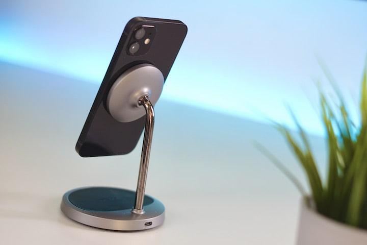 Schwarzes Smartphone haelt magnetisch an einer Ladestation