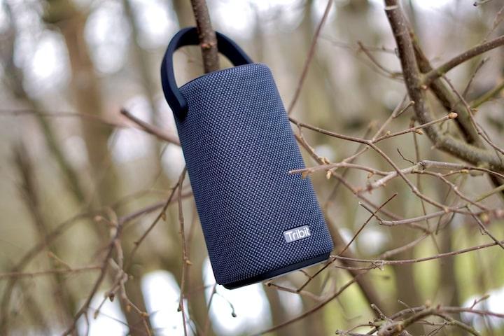Tribit StormBox Pro in schwarz haengt in einem Busch an einem Ast