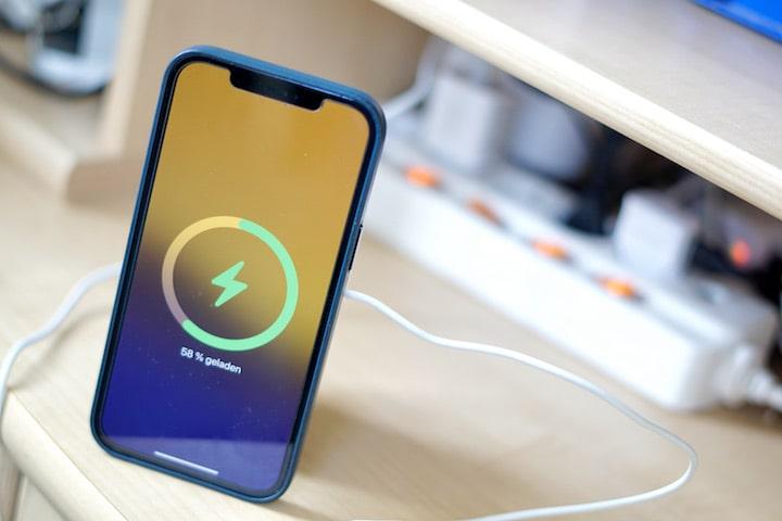 iPhone 12 Pro Max steht vor einer Steckdose und wird kabellos geladen