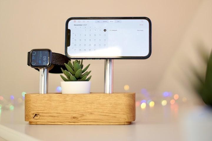 iPhone haengt an einer MagSafe Halterung aus Holz