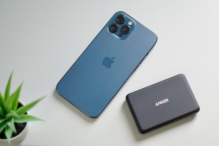 Blaues iPhone liegt neben einem MagSafe Akku auf einem Tisch