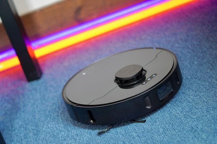 Dreame Bot L10 Pro Saugroboter faehrt ueber blauen Teppich vor Neon Lichtern