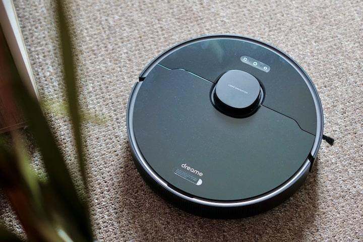 Dreame Bot L10 Pro feahrt ueber Teppich neben einer Pflanze entlang