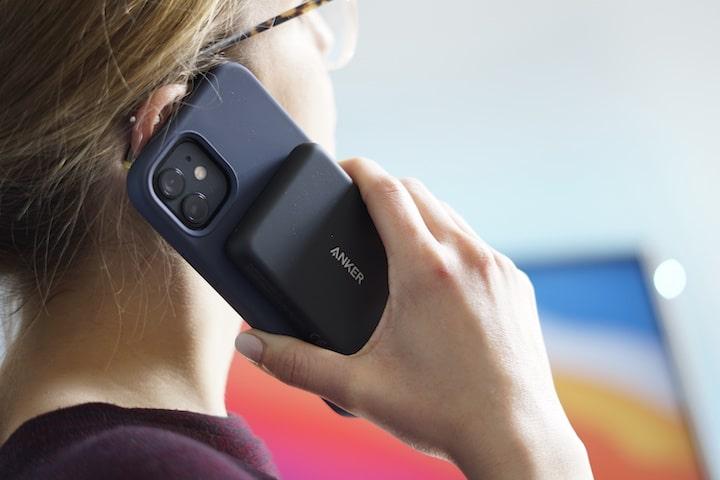 Frau telefoniert mit Smartphone und eine magnetische Powerbank haengt daran
