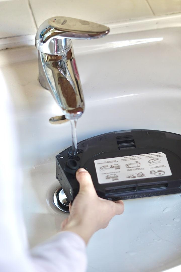 Hand fuellt Wasser in einen Wassertank