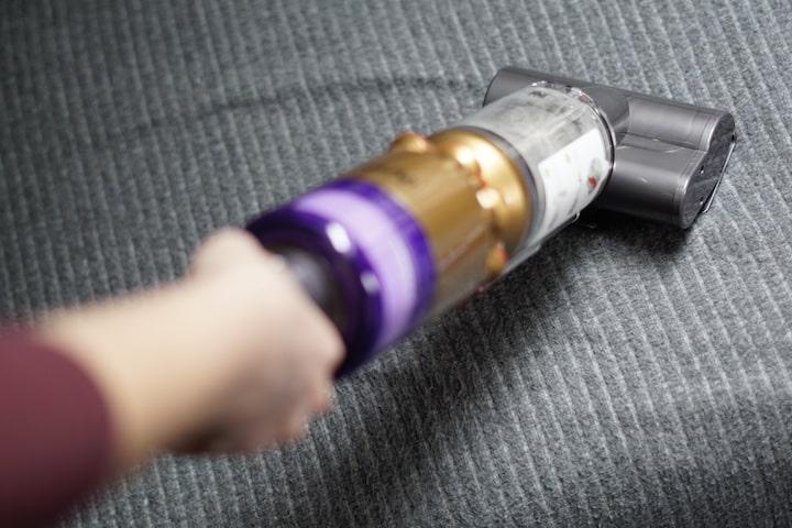 Hand reinigt mit Sauger eine graue Decke
