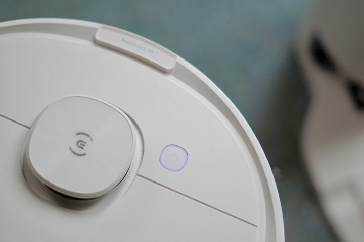 Knopf auf der Oberseite eines automatischen Staubsaugers