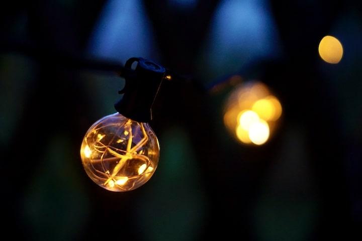 LED Gluehbirne bei Nacht mit Bokeh im Hintergrund