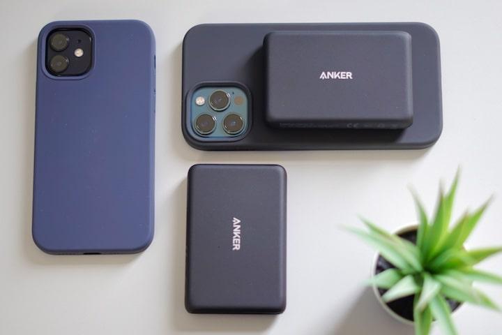 Mehrere iPhones und Powerbanks liegen neben einer Pflanze auf einem Tisch