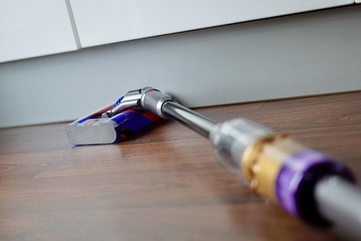 Omni Glide Akkusauger reinigt eine Kante an einem Schrank