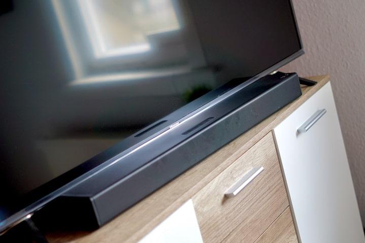 PEAQ PSB 150 Soundbar Lautsprecher liegt auf einem Schrank vor einem TV