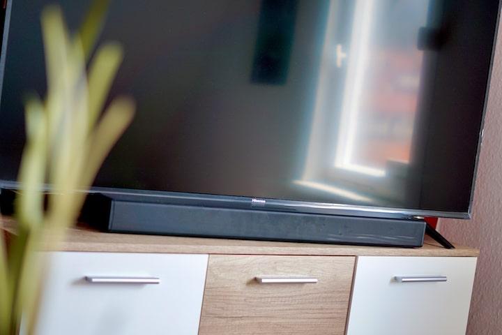 PEAQ Soundbar steht auf Sideboard neben einer Pflanze vor einem TV