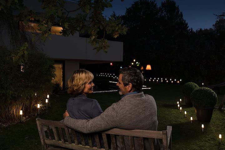 Paar sitzt abends im beleuchteten Garten