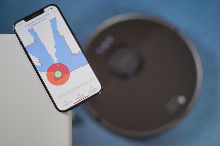 Smartphone mit Xiaomi Home App liegt auf einem Tisch neben einem Saugroboter