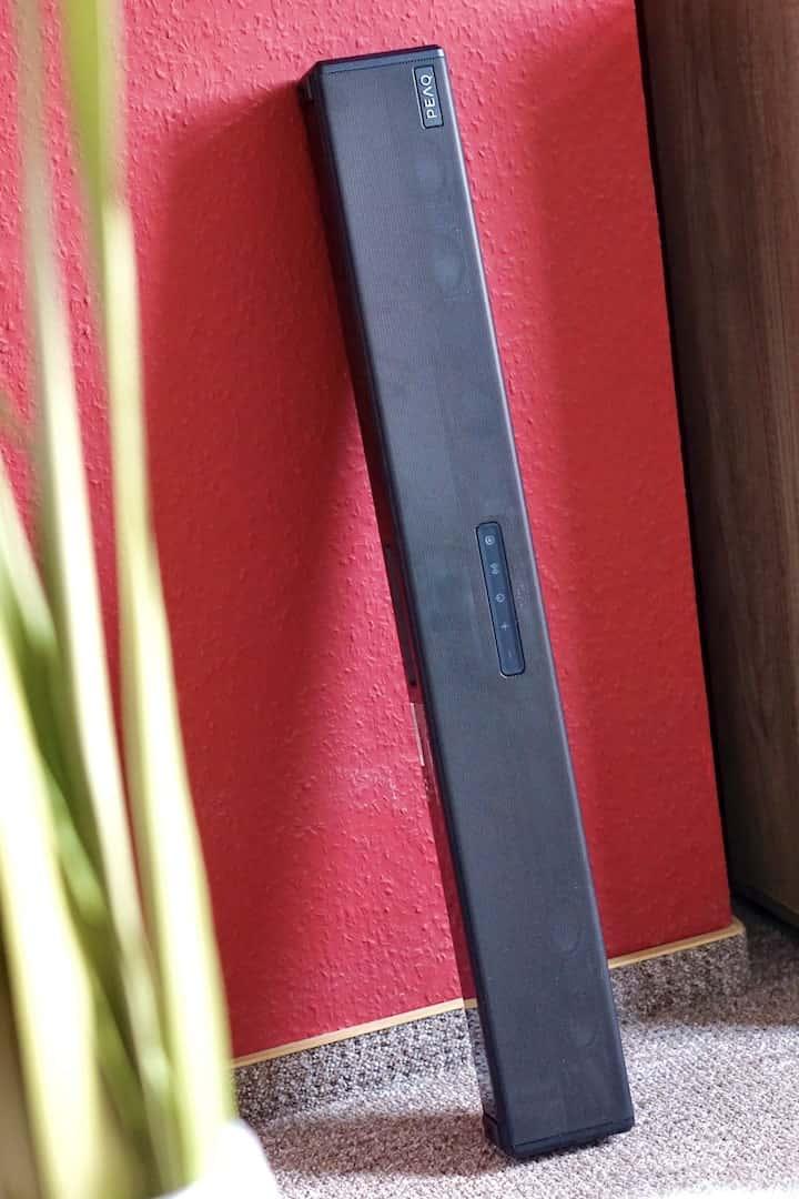 Soundbar steht hochkant an einer roten Wand neben einer Pflanze min