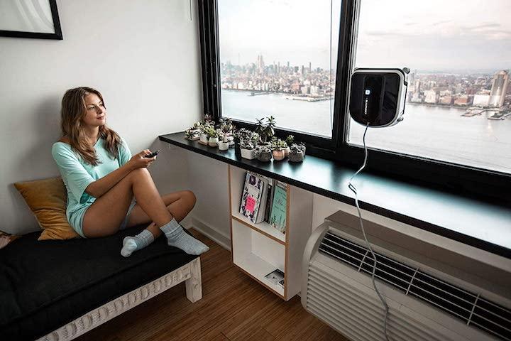 Blaupunkt Bleubot XWIN Vibrate reinigt Fenster neben Frau mit Fernbedienung
