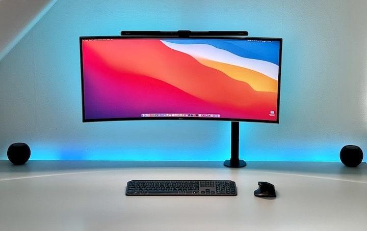 Bunter PC Monitor mit Lampe und Tastatur auf einem Schreibtisch