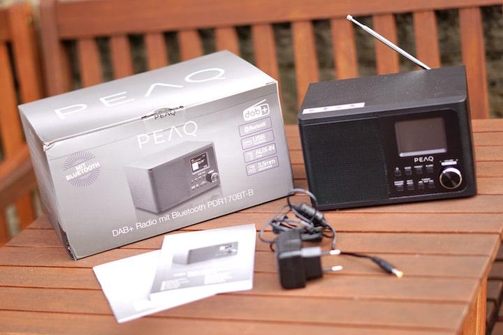 Digitales Radio von PEAQ mit Netzteil Bedienungsanleitung und Lieferumfang auf einem Tisch