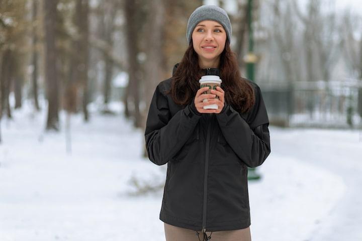 Frau mit GAMMA Jacke und Kaffeebecher im Schnee min
