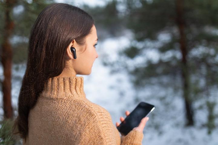 Frau traegt MOBI Kopfherer und hat Handy in der Handy