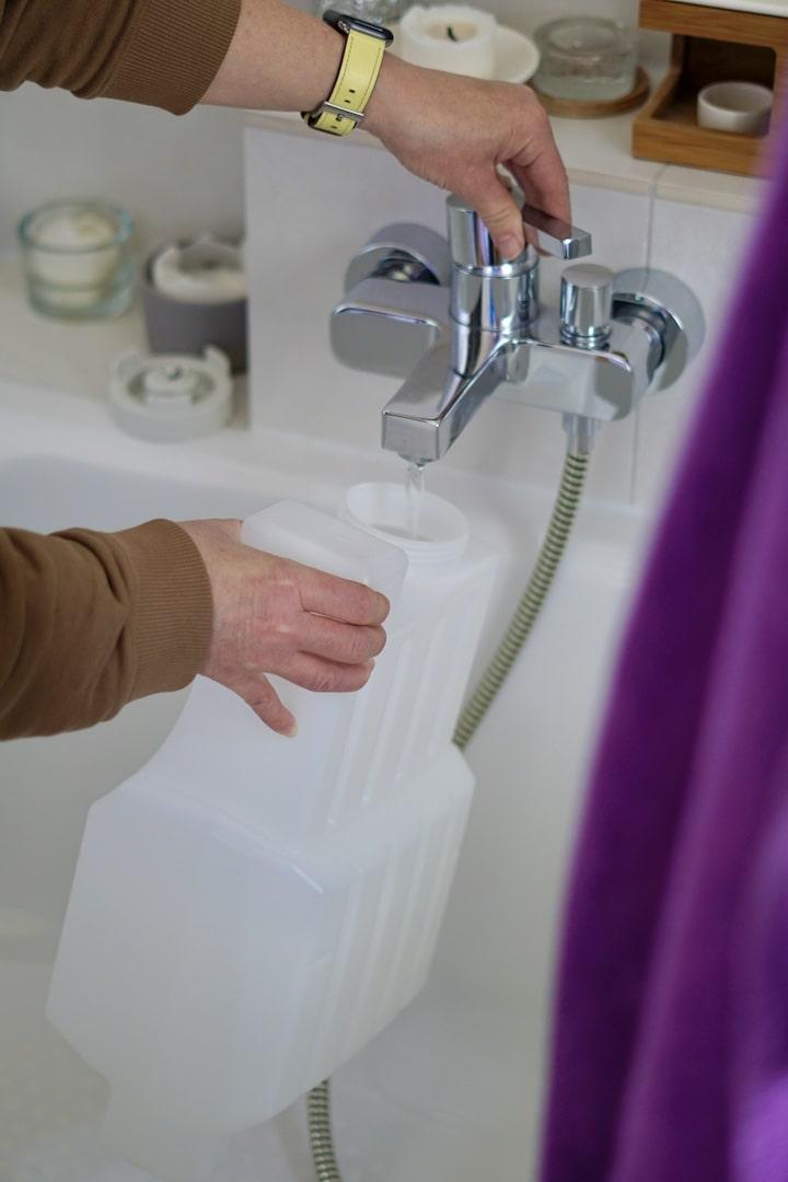 Hand am Wasserhahn fuellt einen Wassertank auf