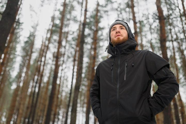 Mann mit Funktionsjacke im Wald min