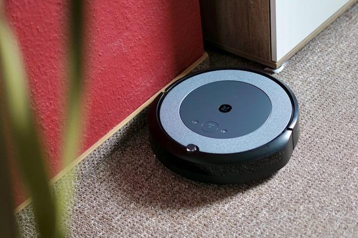 Saugroboter reinigt Kanten in einem Raum mit Teppichboden