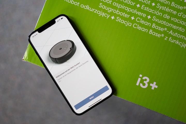 Smartphone mit iRobot App liegt auf gruenem Untergrund