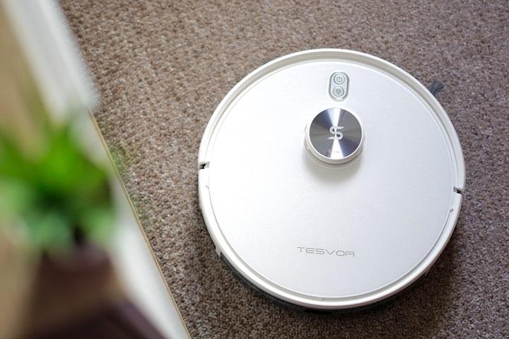Tevsor S6 Turbo Saugroboter steht auf einem Teppich neben einer Pflanze