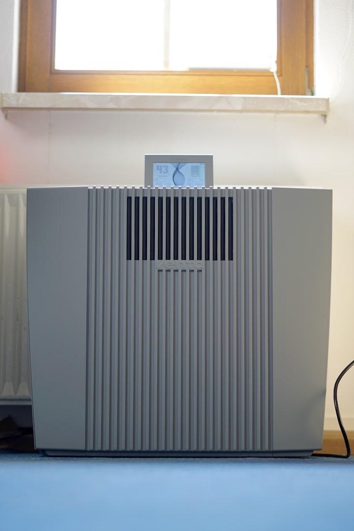 VENTA Professional AH902 Luftreiniger steht an einer Wand auf blauem Teppich