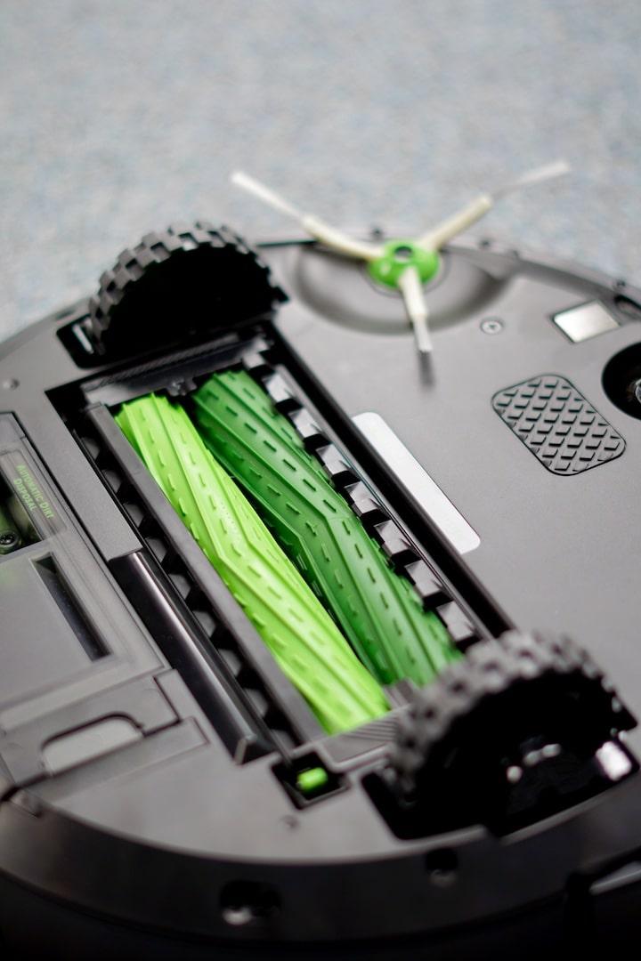 Zwei gruene Rollen und Buersten auf der Unterseite eines iRobot