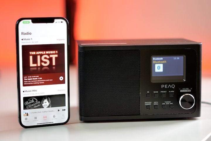 iPhone steht neben Digitalradio vor rotem Hintergrund