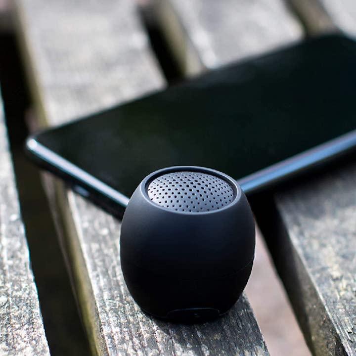 Boompods Zero in schwarz neben Handy