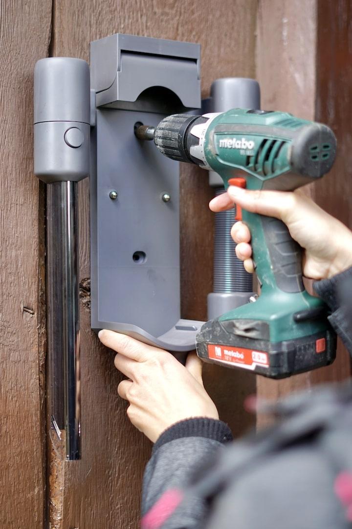 Frau montiert mit Akkuschrauber eine Wandhalterung an Holz