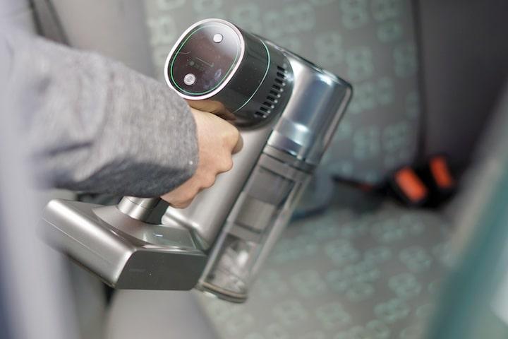 Hand mit Dreame T30 Staubsauger saugt einen Autositz