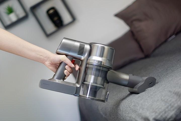Kompakter Akkusauger reinigt eine Decke auf einem Sofa