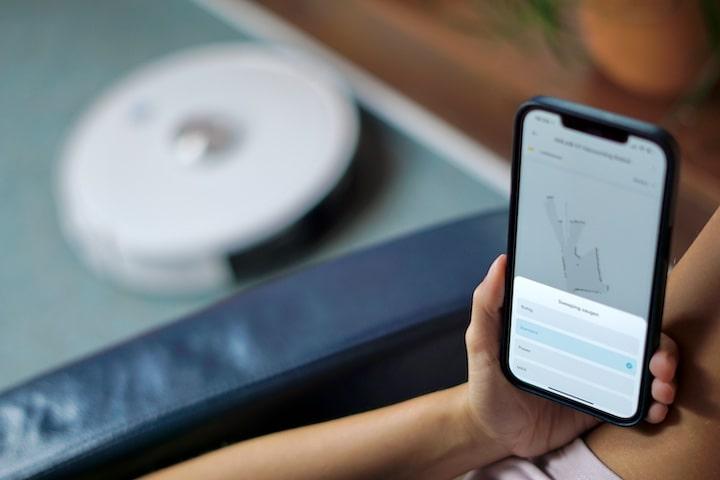 Hand mit iPhone steuert Saugroboter mit einer App