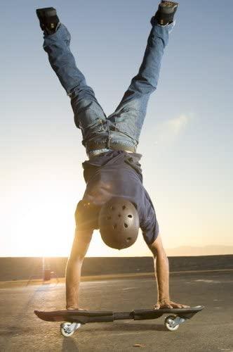 Mann macht Handstand auf Waveboard