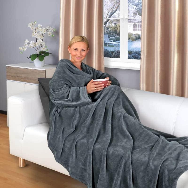 Frau mit Kuscheldecke auf dem Sofa