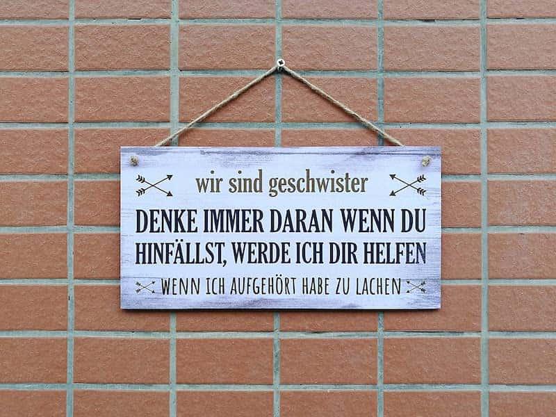 Schild mit Spruch zu Geschwistern an einer Wand