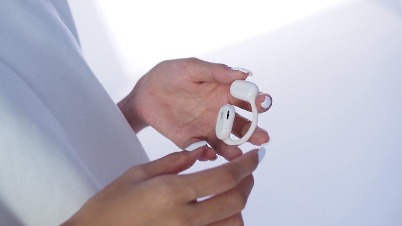 Frau mit wei%C3%9Fen Oladance Kopfhoerern in der Hand